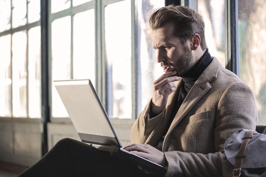 Homme qui se questionne au sujet des massages ou thérapies devant son laptop.