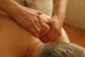 Masseur relaxant l'épaule d'un homme