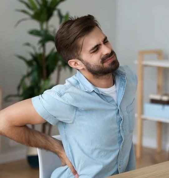 Jeune homme ayant mal au dos et nécessitant un massage
